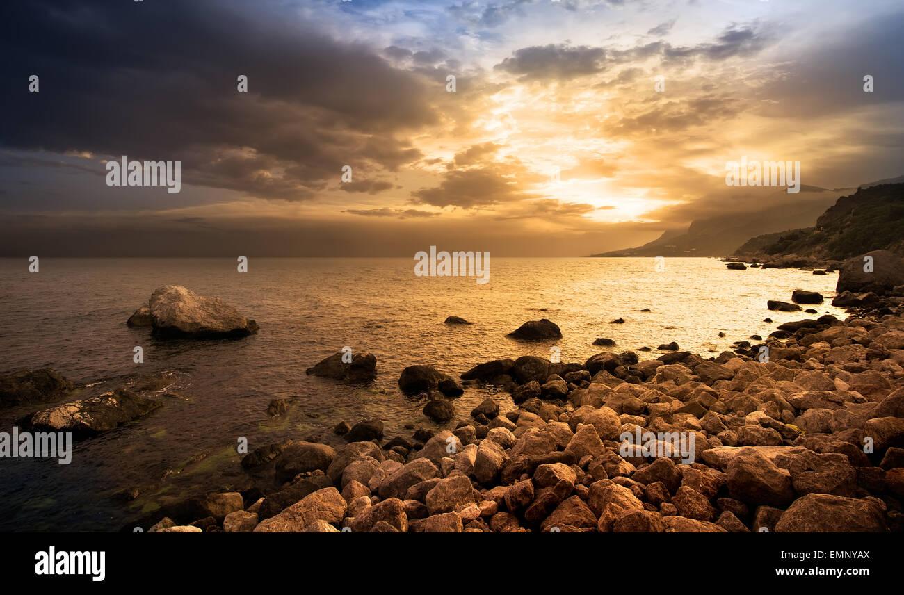 Magnifique coucher de soleil sur les roches par la mer Photo Stock