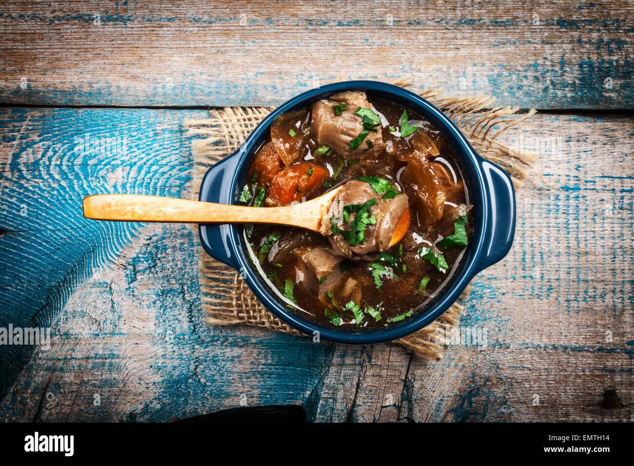 Ragoût de viande avec légumes et fines herbes sur la vieille table en bois Photo Stock