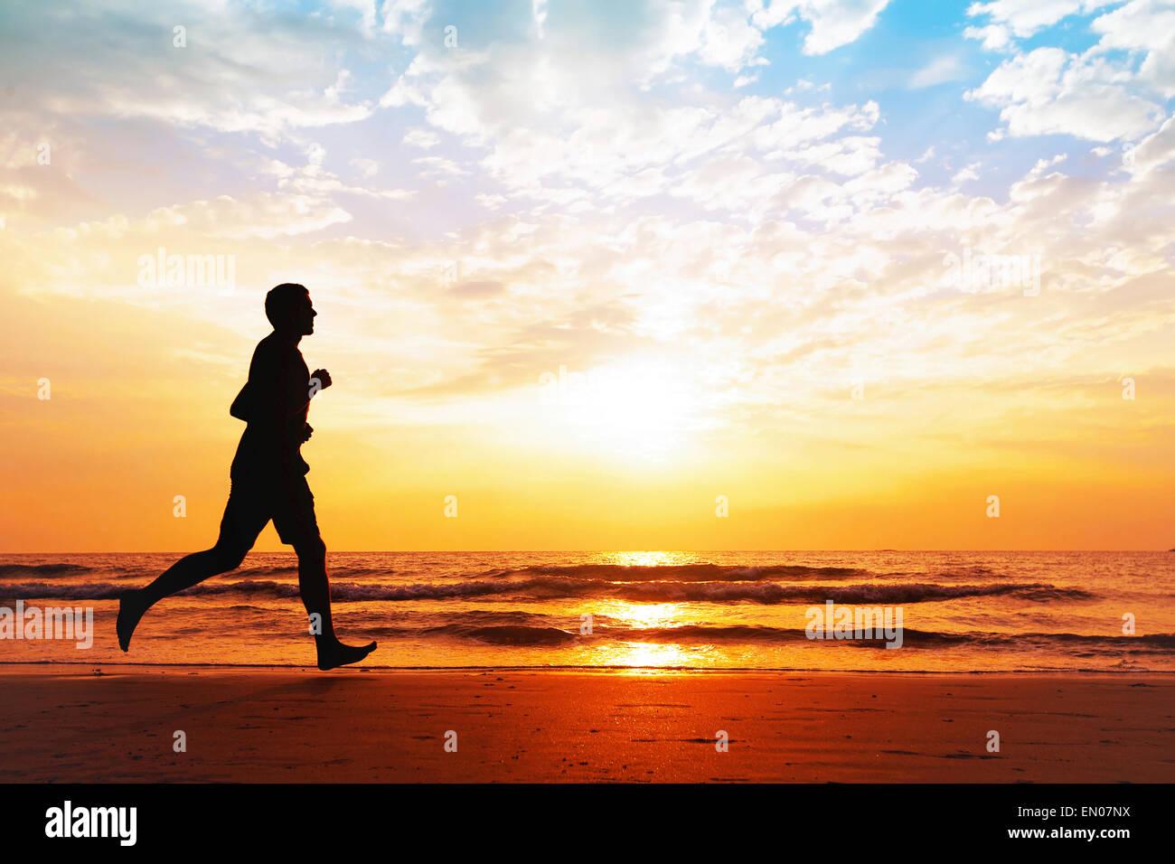 Vie saine et active, la silhouette de l'homme le jogging sur la plage Photo Stock