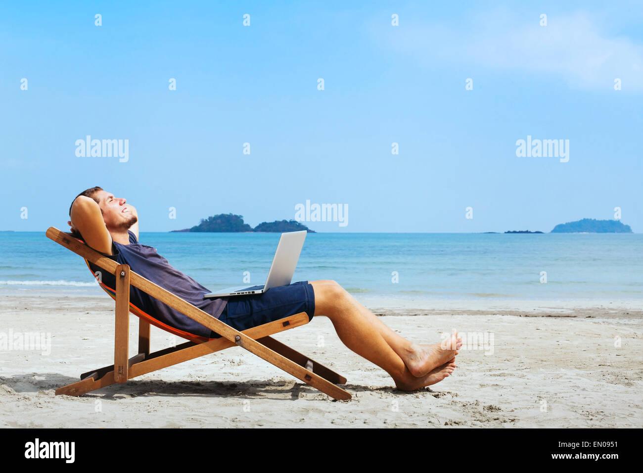 Smiling businessman with computer détente sur la plage Photo Stock