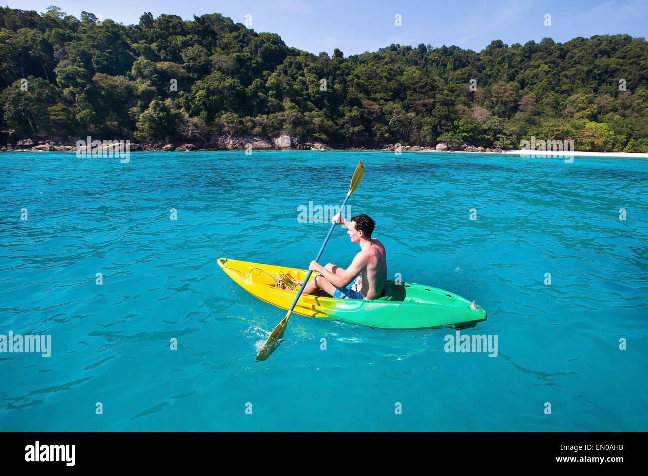 Young caucasian man en kayak près de Paradise Island dans l'eau turquoise Photo Stock