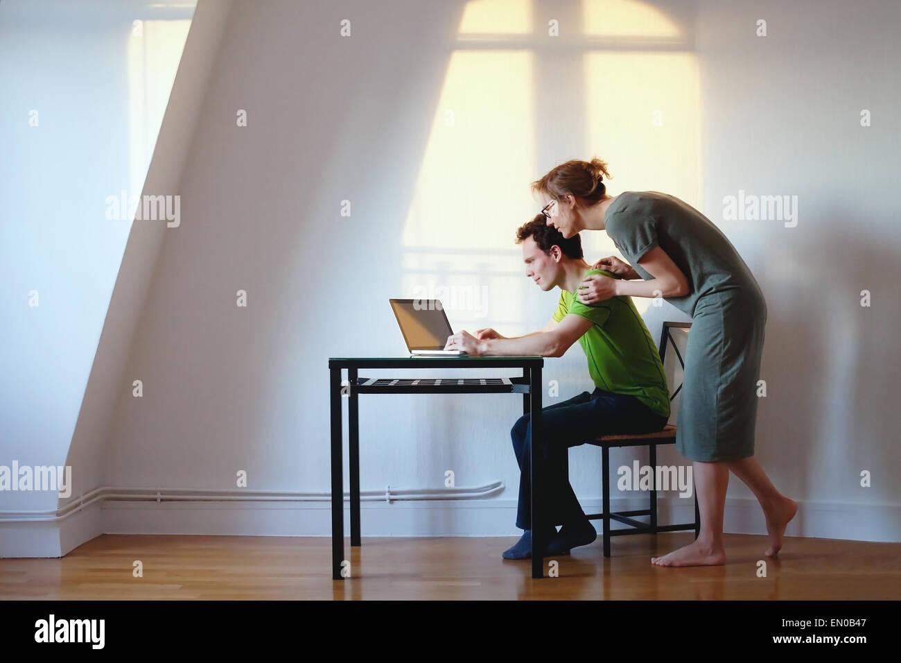 Jeune couple à la recherche à l'ordinateur portable à leur domicile, à l'intérieur Photo Stock