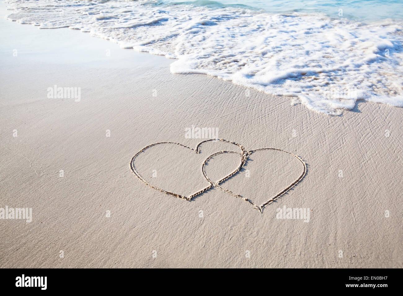 Deux cœurs dessinés sur le sable blanc de la plage Paradise Photo Stock