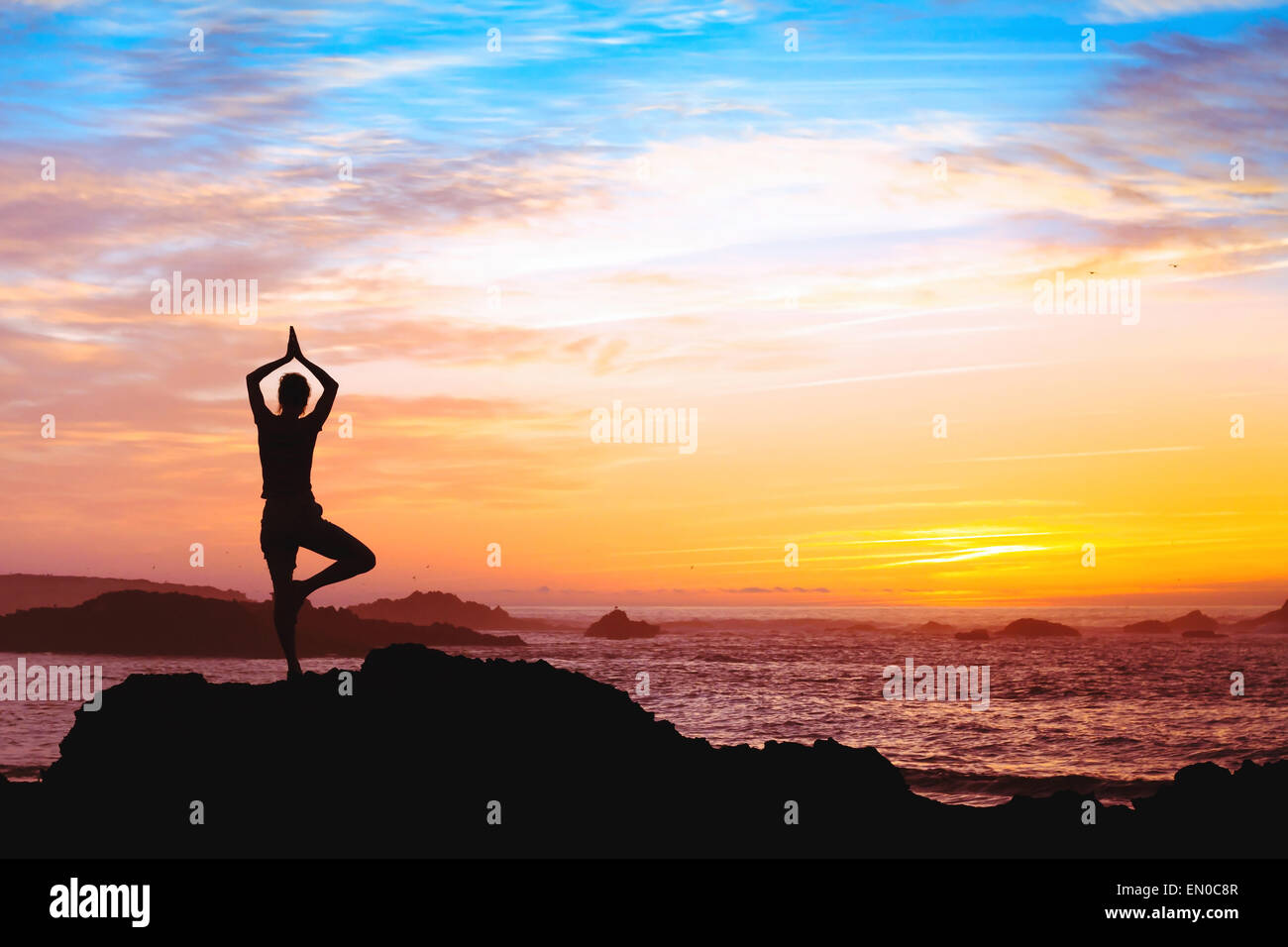Belle silhouette of woman practicing yoga près de la mer Photo Stock