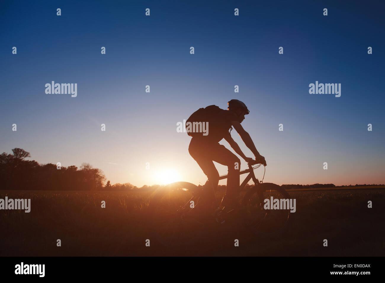 Silhouette de jeune homme sur le vélo au coucher du soleil Photo Stock