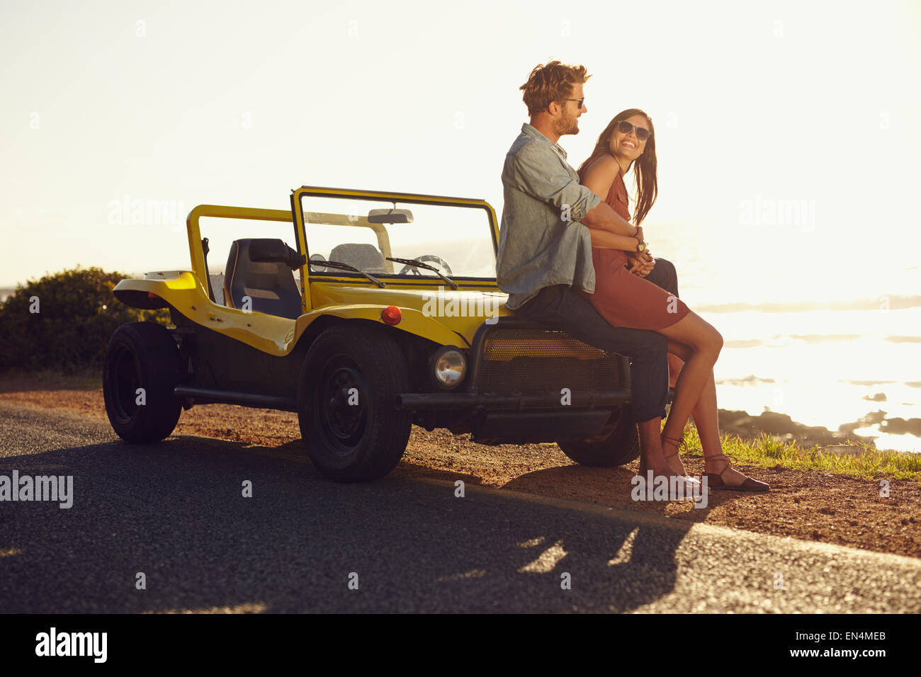 Aimer jeune couple assis sur le capot de leur voiture tandis que dehors sur un roadtrip. Caucasian couple ensemble Photo Stock