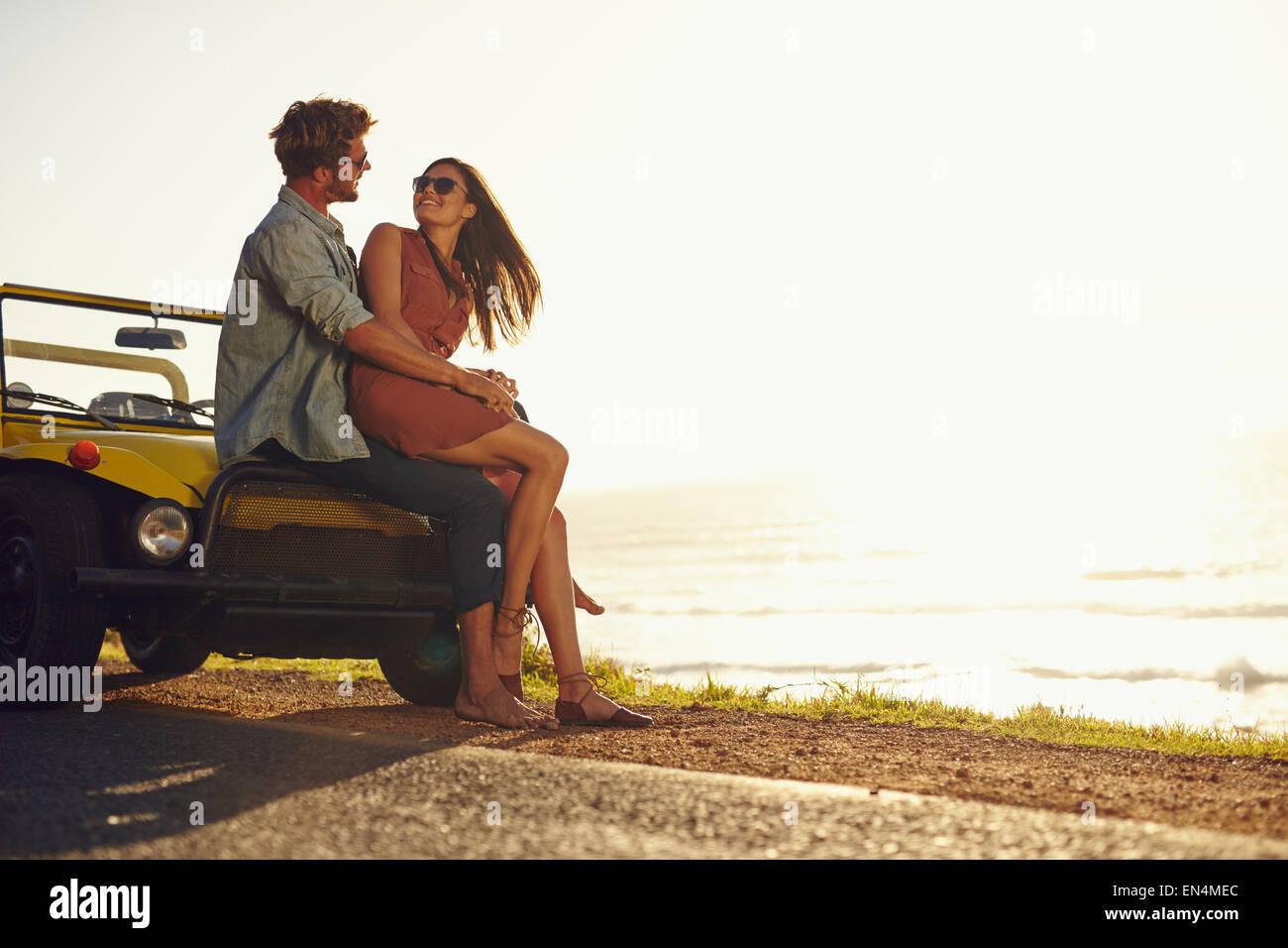 Jeune couple se regarder dans les yeux. Couple assis sur le capot de leur voiture profitant de l'instant. Photo Stock