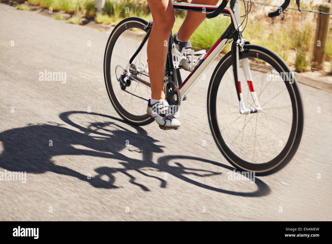 La section basse image de woman riding bicycle on country road. Portrait de l'athlète féminine de cyclisme. Photo Banque D'Images