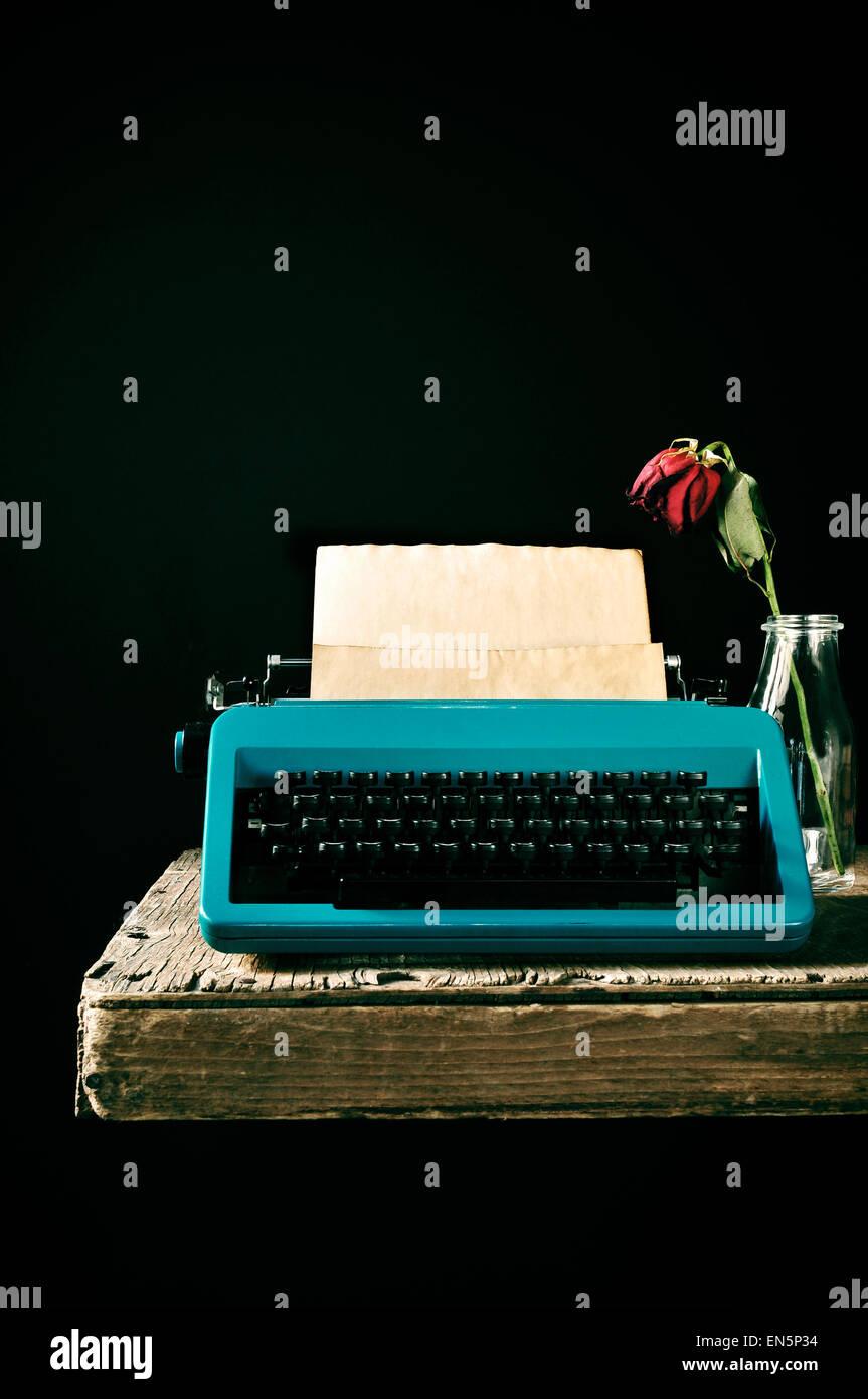 Une vieille machine à écrire en bleu sur une page blanche dans son rouleau et une rose rouge fanée dans un vase en verre sur une table en bois rustique, contre Banque D'Images