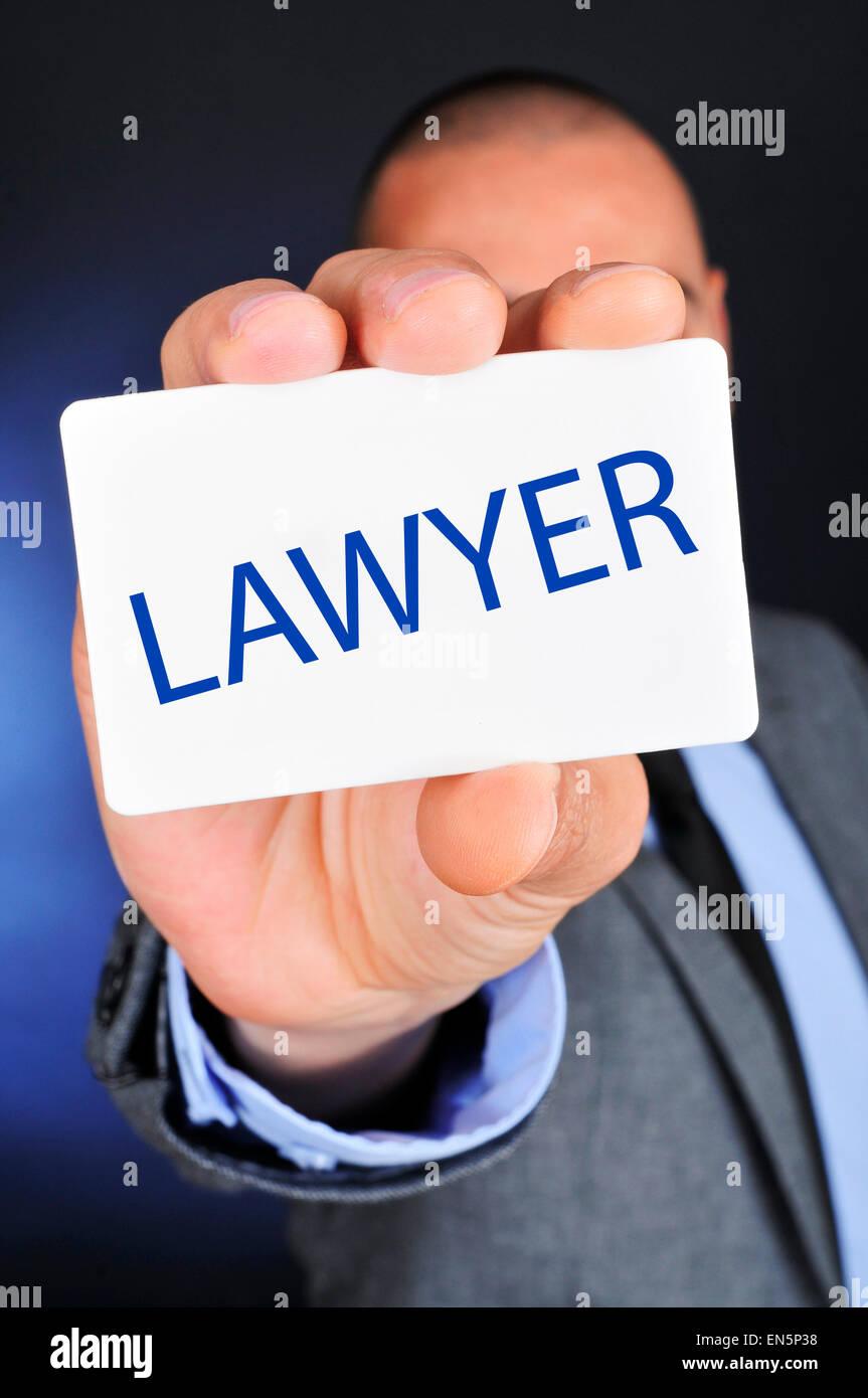 Un jeune homme de race blanche portant un costume gris montre une pancarte avec le mot avocat écrit en c Photo Stock