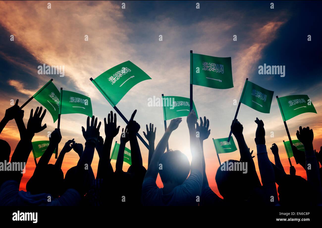 Silhouettes de gens tenant un drapeau de l'Arabie Saoudite Photo Stock