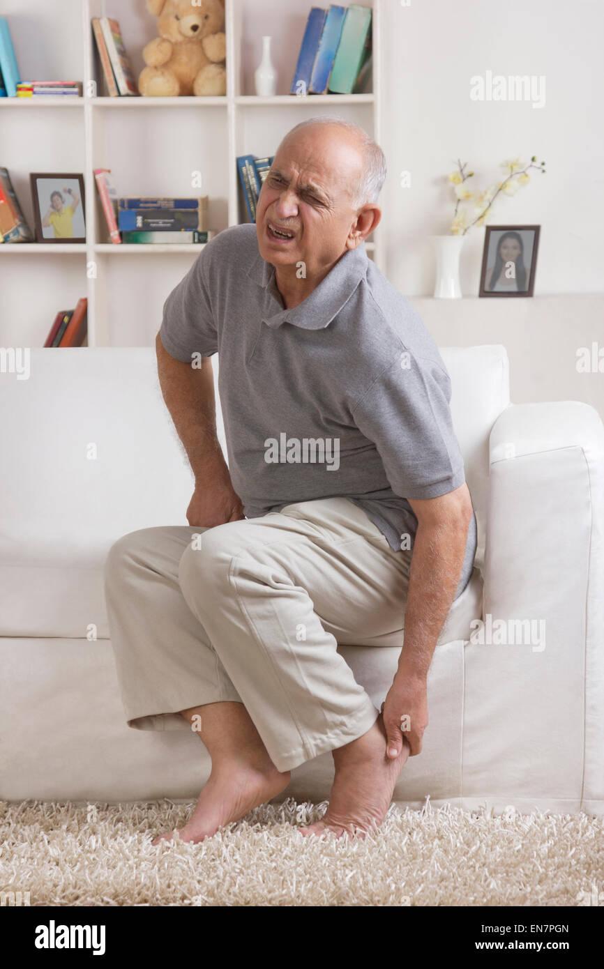 Vieil homme avec douleur dans le pied Photo Stock