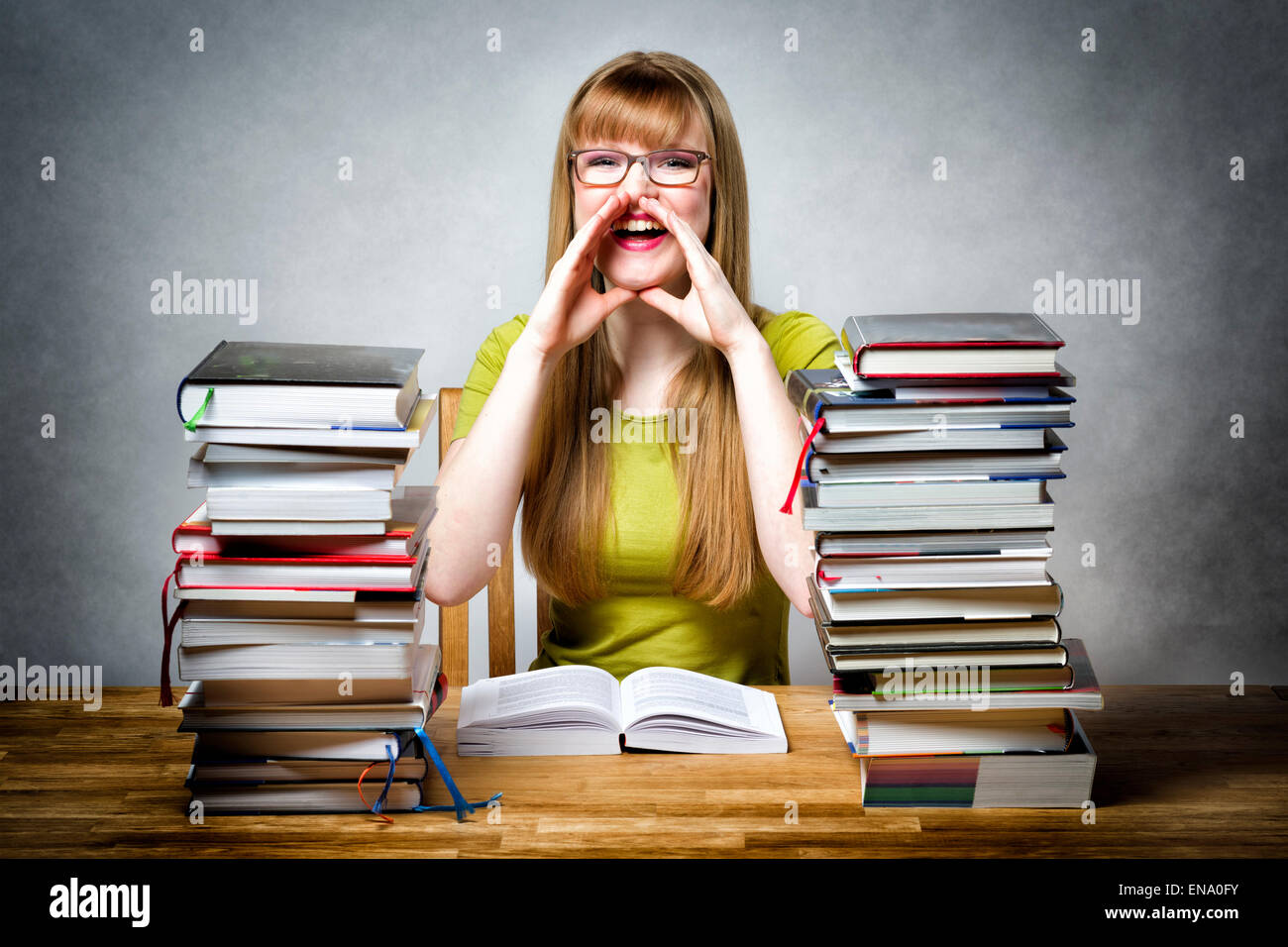 Heureux lycéenne sitting at desk with books, tenant ses mains devant sa bouche et demande quelque chose Photo Stock