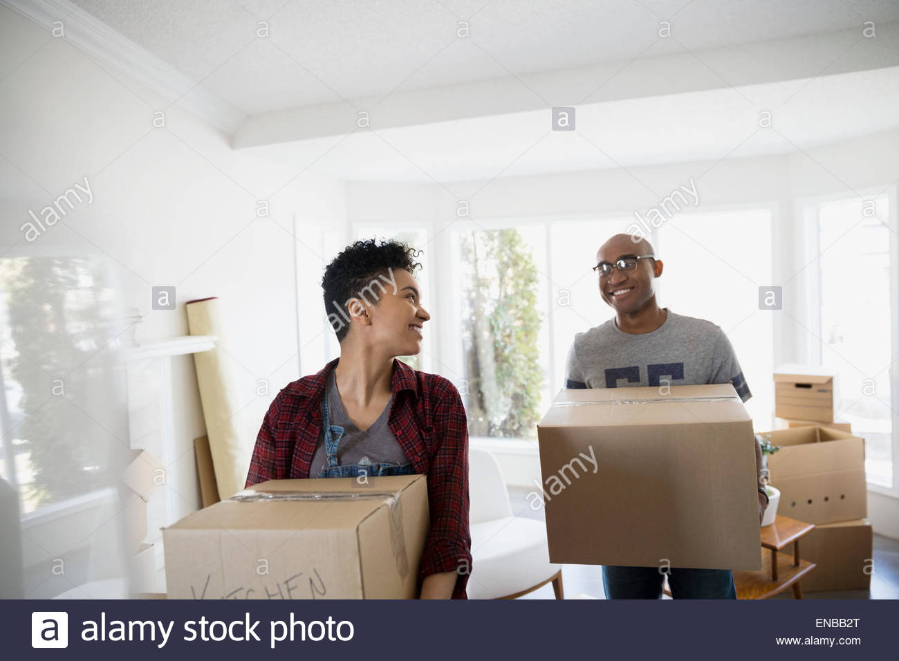 Couple carrying boxes in living room Photo Stock