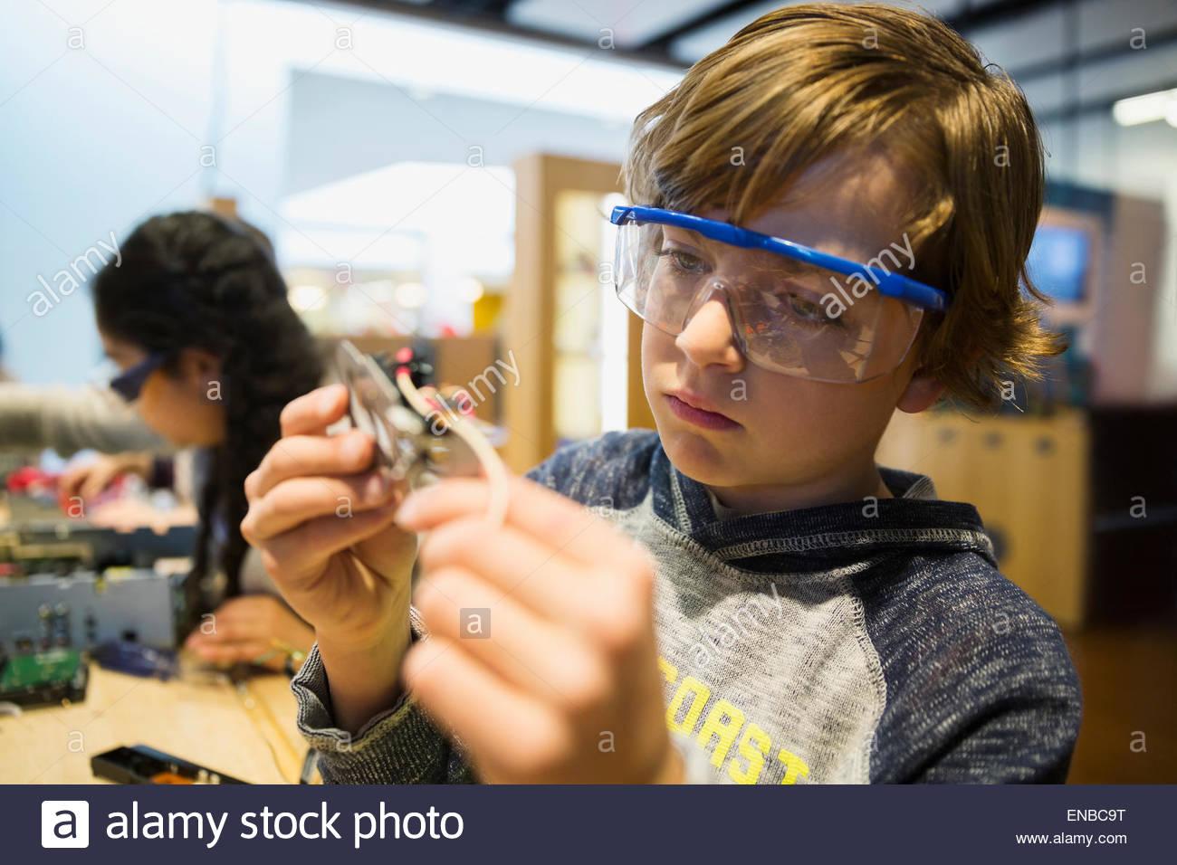 Garçon curieux assemblage circuit électronique à science center Photo Stock