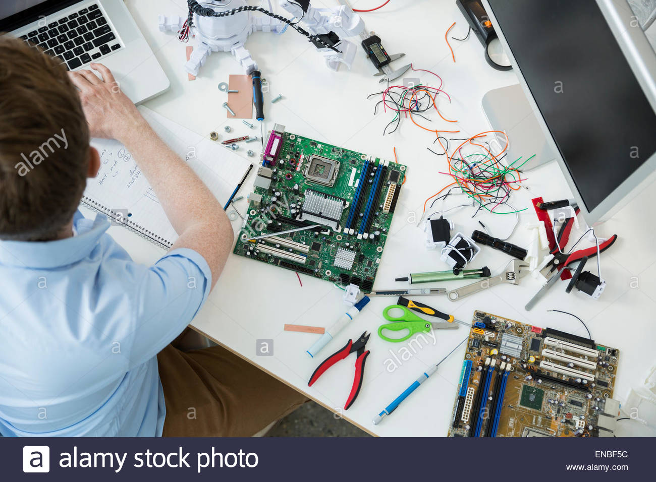 L'assemblage de circuits imprimés et ingénieur working at laptop Photo Stock