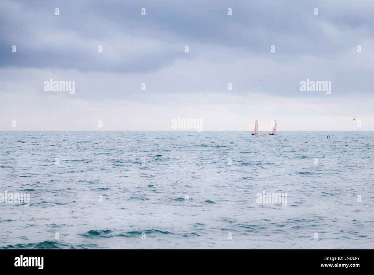 Deux sauts de voile sur l'horizon, regardez tout petit sur l'océan sous un grand ciel noir. Photo Stock