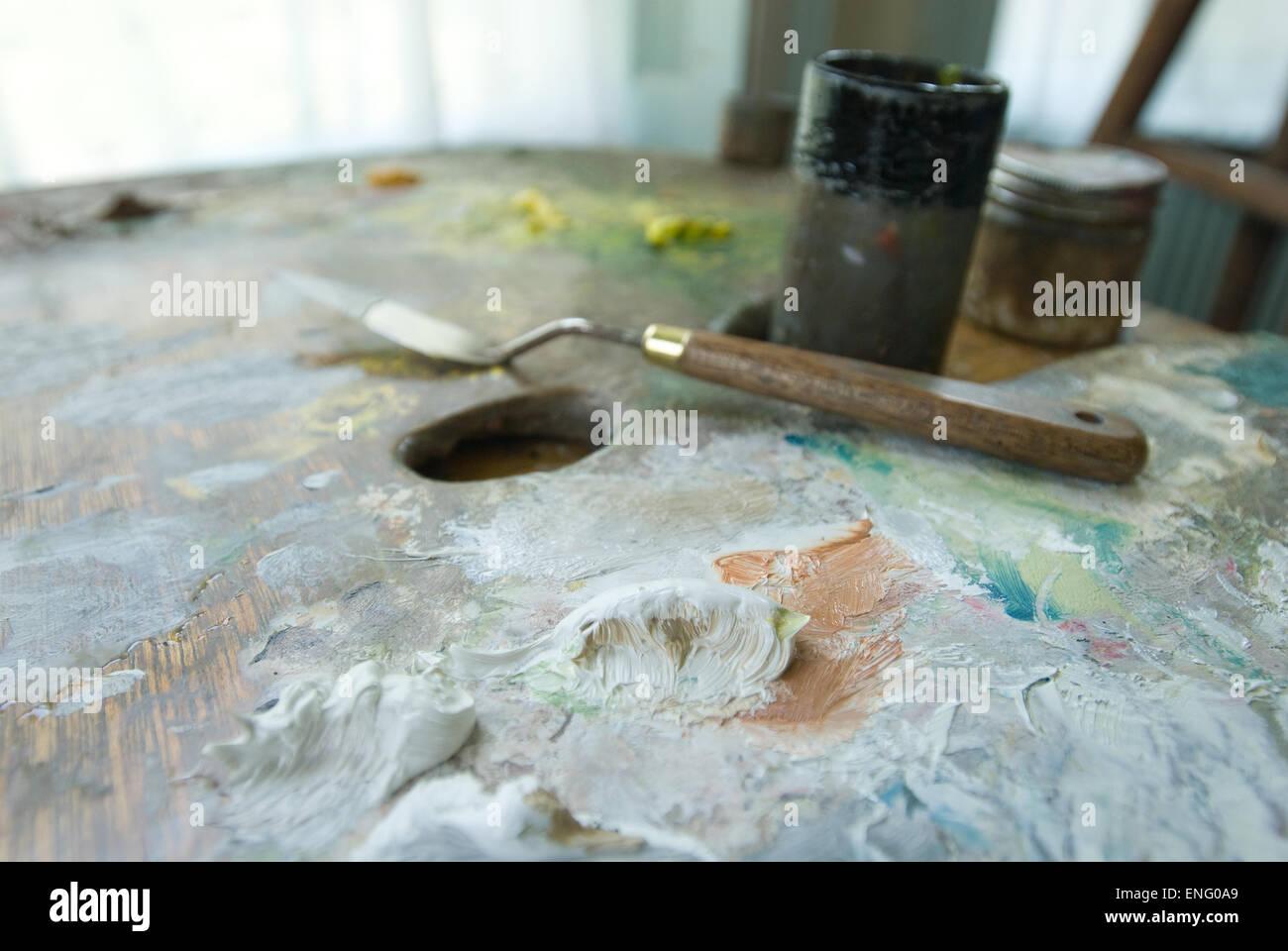 Huiles mixtes peinture blanche sur les grands peintres palette avec un couteau et soupçon de studio en arrière-plan Banque D'Images