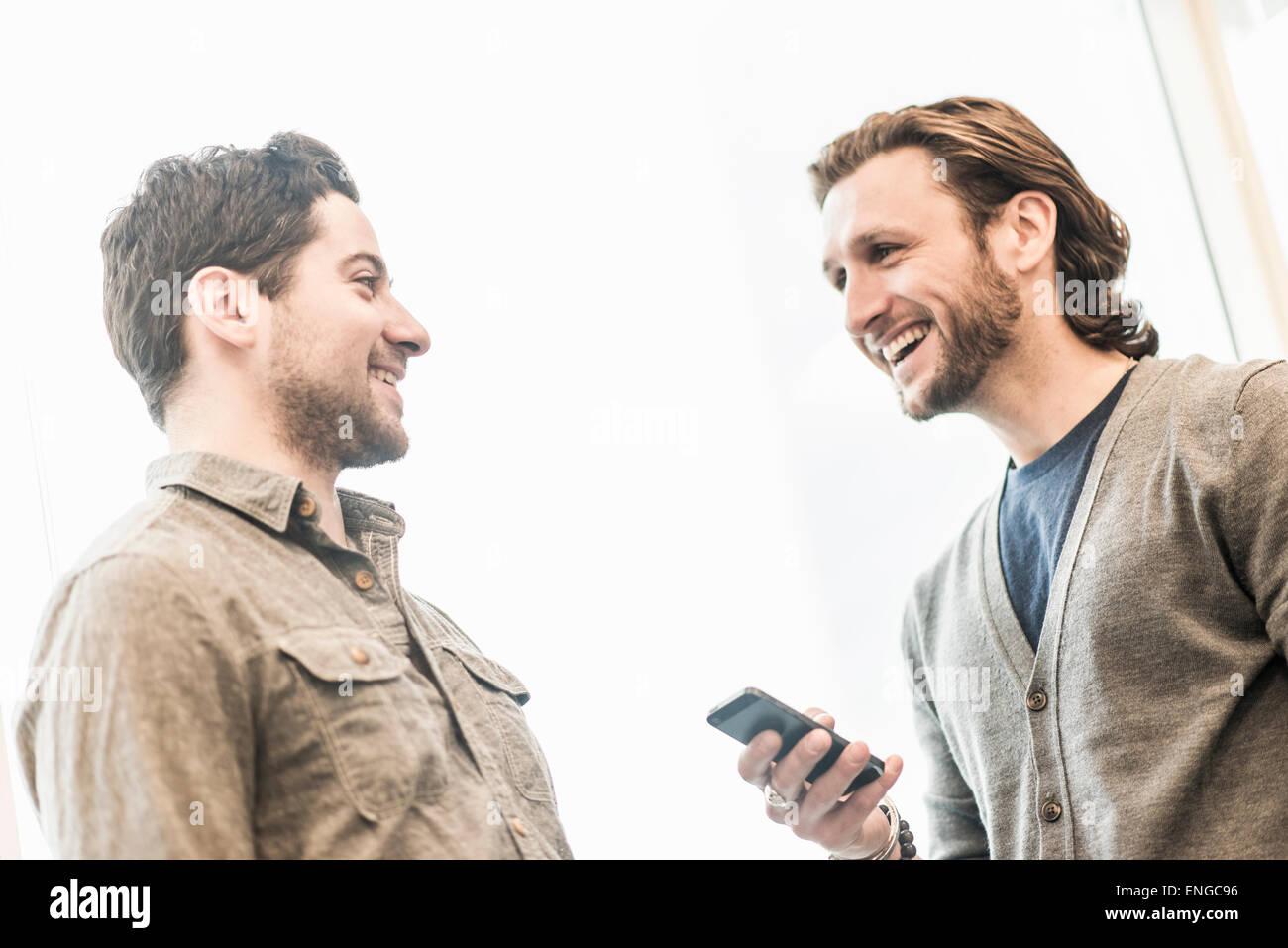 Deux hommes souriant, l'un tenant un téléphone intelligent. Photo Stock