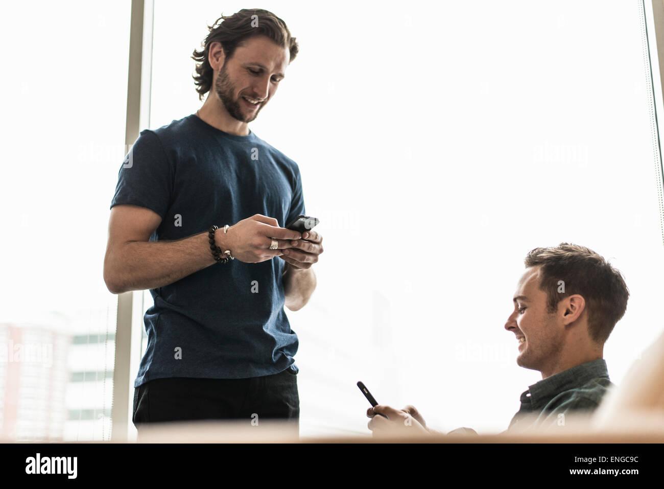 Deux hommes dans un bureau, la vérification de leurs téléphones intelligents. Photo Stock