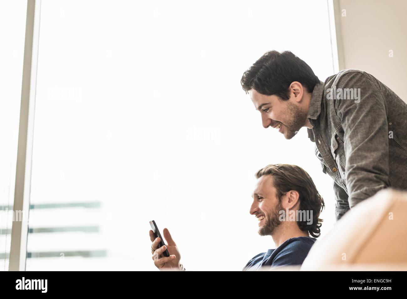Deux hommes d'affaires à la recherche à un téléphone intelligent et souriant. Photo Stock