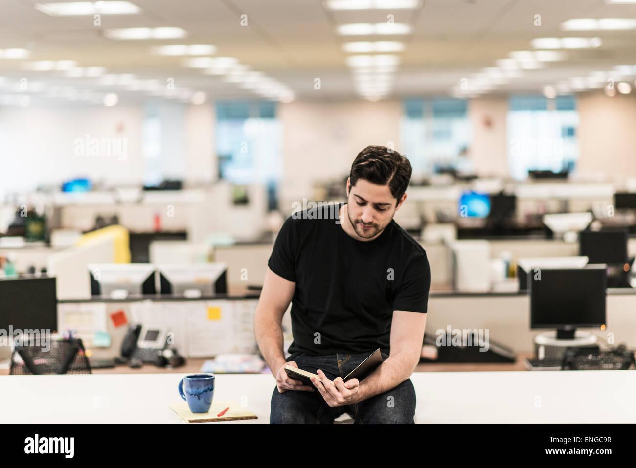 Un homme assis sur un bureau dans un bureau à la recherche d'un livre ou d'un journal. Photo Stock