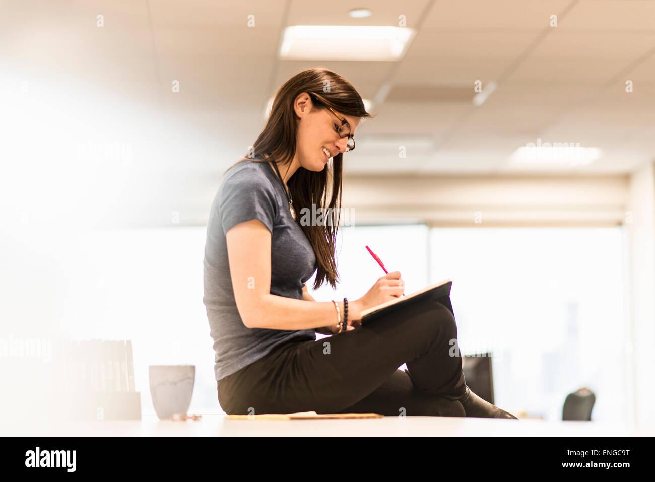 Une jeune femme assise sur son bureau par écrit dans un cahier avec un stylo rouge. Banque D'Images