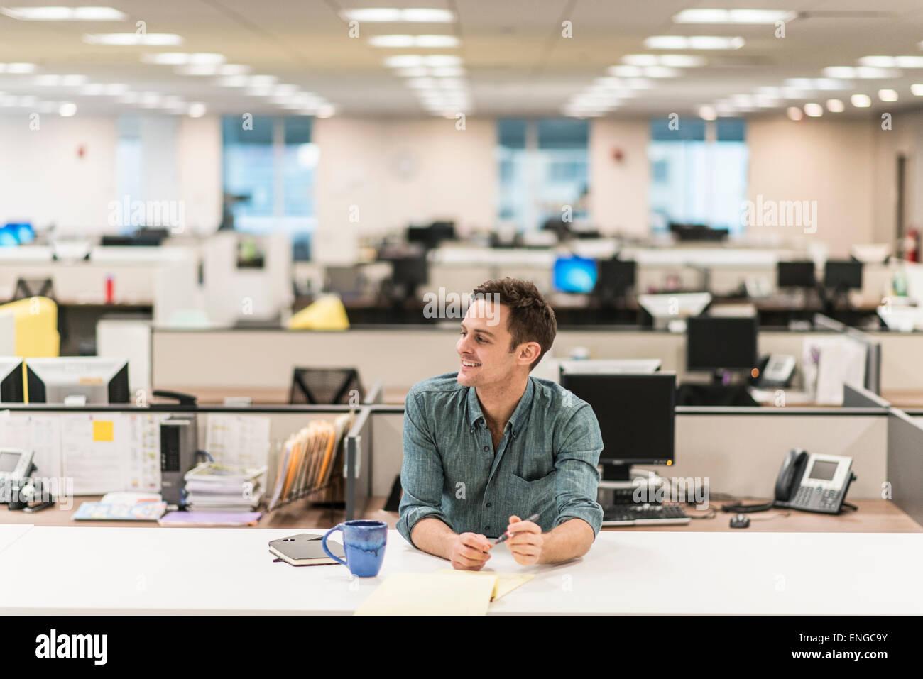 Un jeune homme assis à un bureau dans un bureau. Photo Stock
