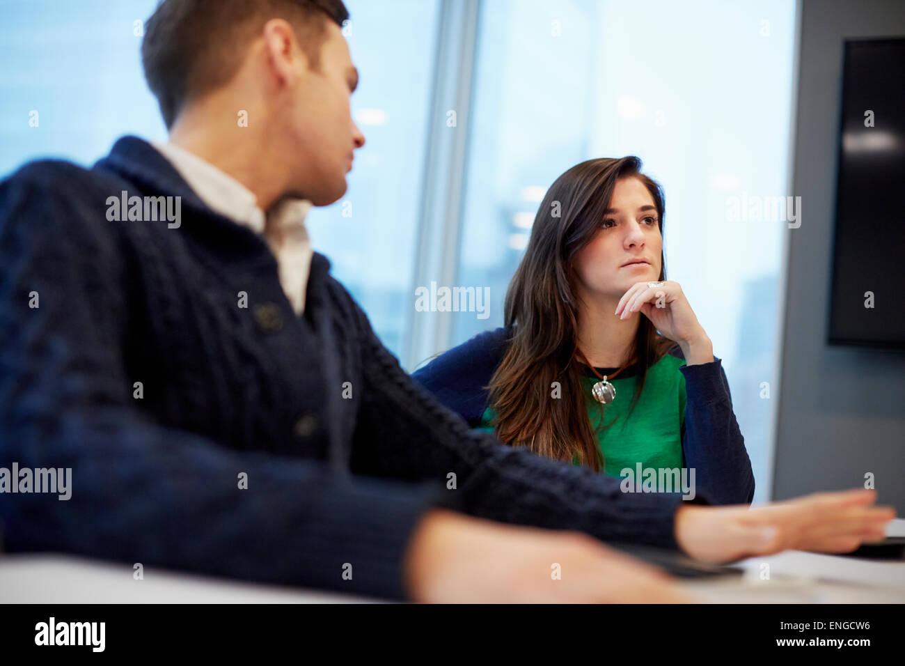 Un homme et une femme assis à une réunion dans un bureau. Photo Stock