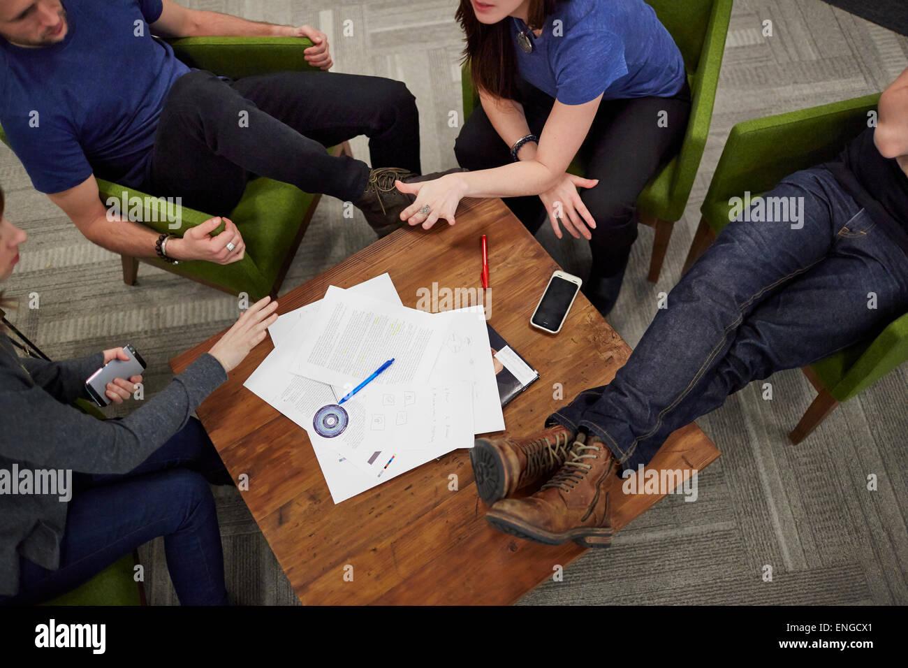 Vue aérienne d'une réunion de quatre personnes assises autour d'une table basse. Photo Stock