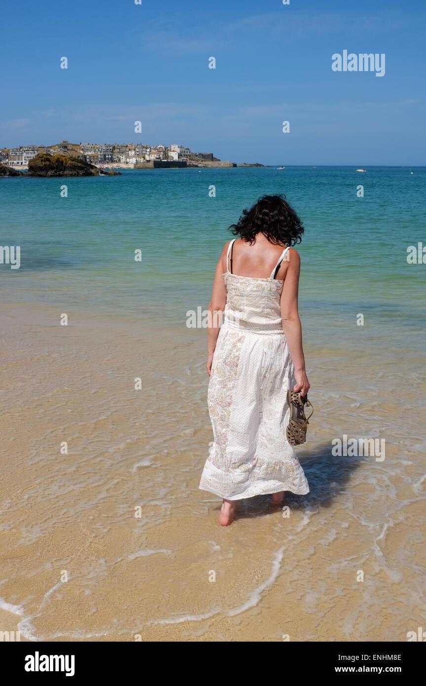 St Ives, Cornwall: femme en robe d'été balade au bord de l'eau sur la plage de porthminster à St Ives sur la côte Banque D'Images