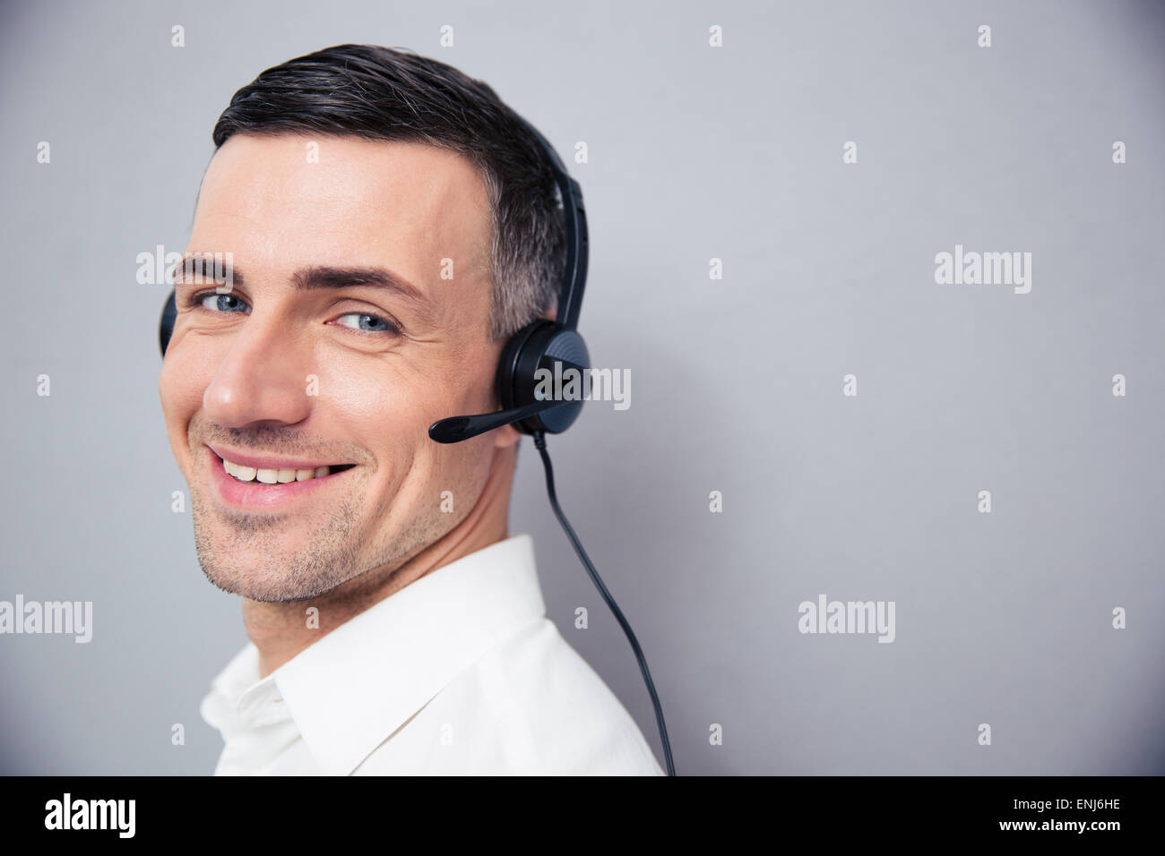 Cheerful businessman in headphones debout sur gray backgorund et looking at camera Banque D'Images