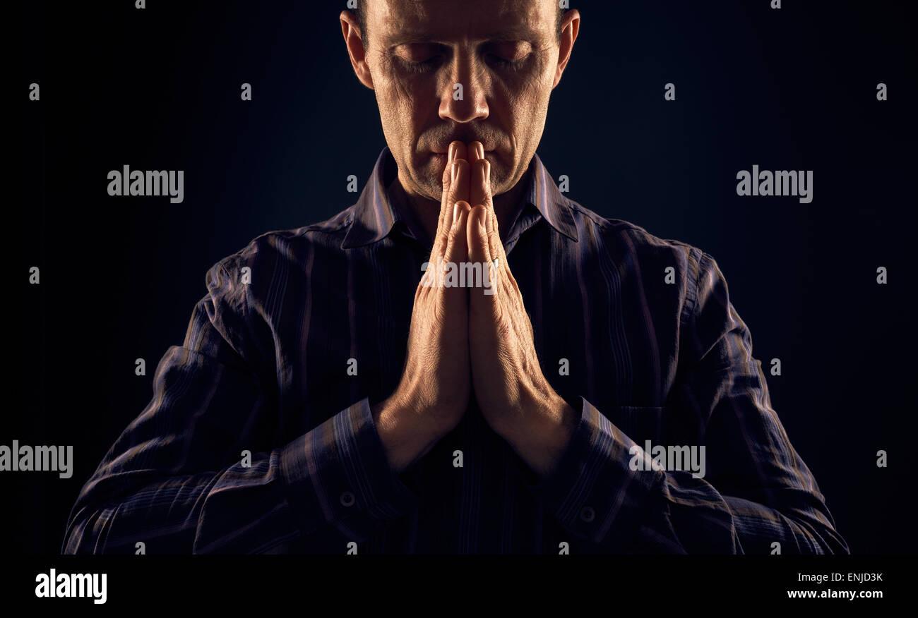 En vue de face d'un homme priant dans l'obscurité avec un rayon de soleil qui brille sur lui Photo Stock
