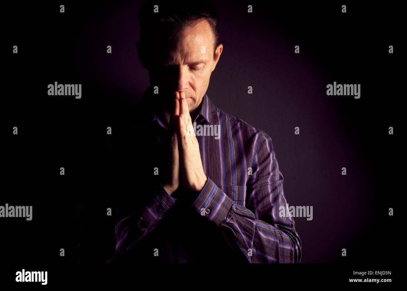 En vue de face d'un homme priant dans l'obscurité à la lumière qui brille sur le côté Photo Stock