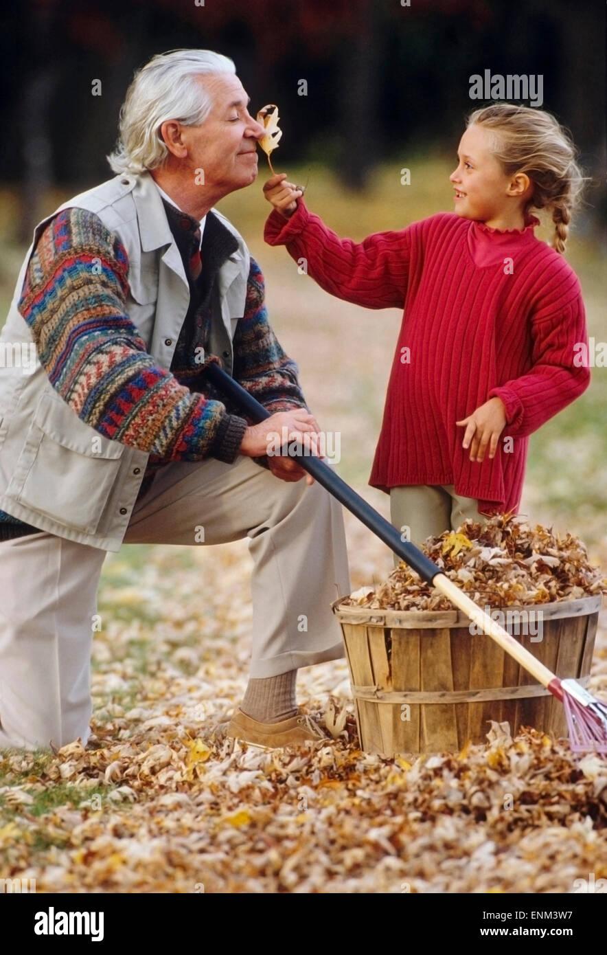 Grand-père et sa petite-fille avec des feuilles Photo Stock