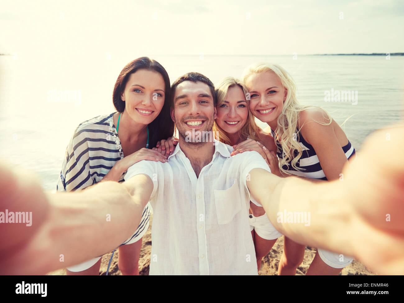 Happy friends sur plage et prendre des selfies Photo Stock