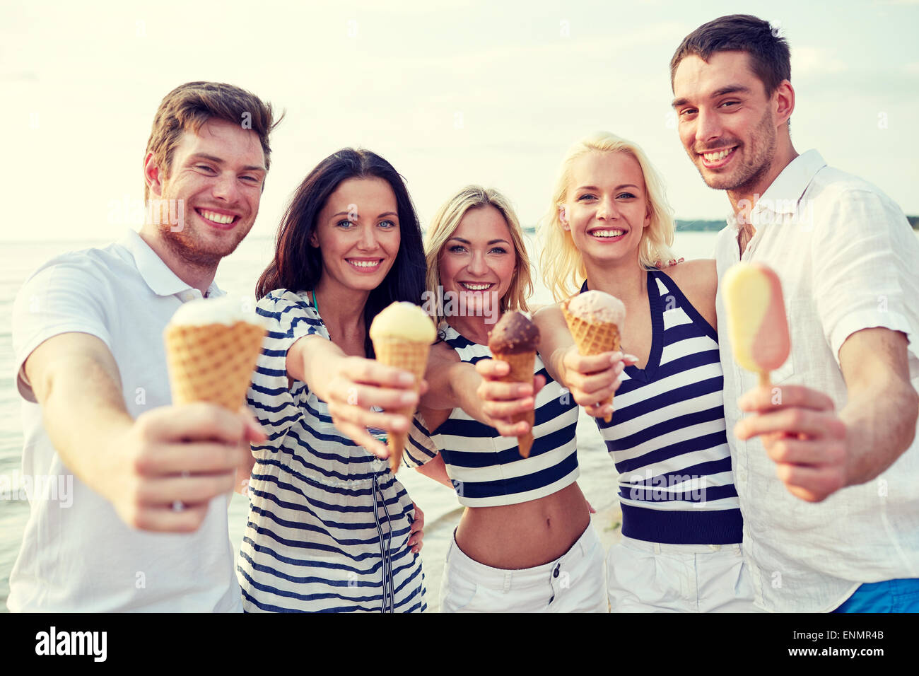 Smiling friends eating ice cream on beach Banque D'Images