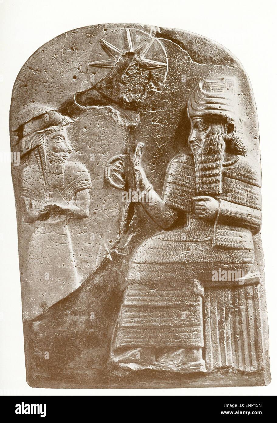 """La figure sculptée à gauche s'Hammourabi, debout devant Shamash, le dieu soleil et """"Seigneur de jugement."""" Le disque au-dessus et entre les deux chiffres représente un disque solaire. Hammourabi est un roi de Babylone de 1792 à 1750 avant J.-C. et est connu pour l'ensemble de lois appelé le Code d'Hammourabi, l'un des premiers codes de lois écrites, qui ont été inscrits au-dessous d'une scène similaire sur une stèle de diorite noire qui mesurait plus de 8 pieds de hauteur. Banque D'Images"""