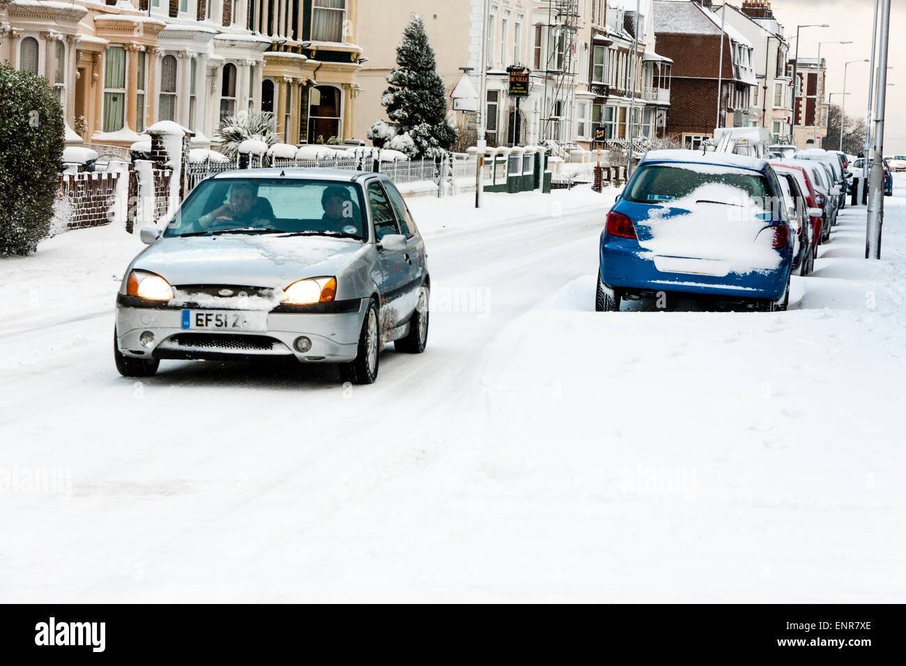 Vue le long de la rue enneigée de Ramsgate en Angleterre après une lourde chute de neige. Voitures garées dans la neige, monovoiture roulant le long de la route. Banque D'Images