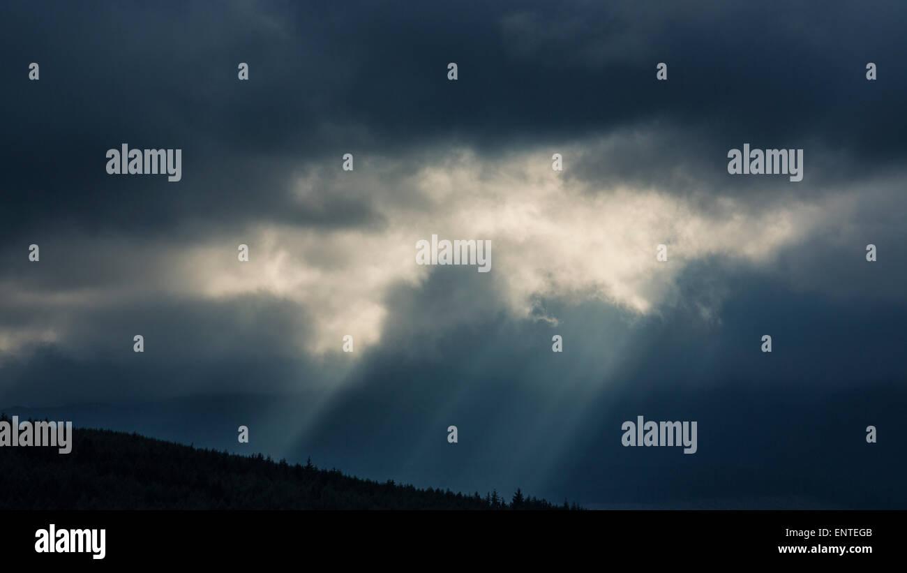 Les rayons du soleil percer les nuages dans un ciel d'orage, UK Photo Stock