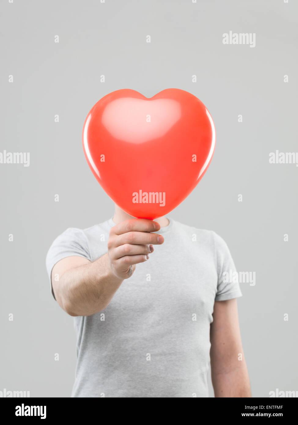 Caucasian man holding ballon en forme de coeur en face de sa tête, contre l'arrière-plan gris Photo Stock