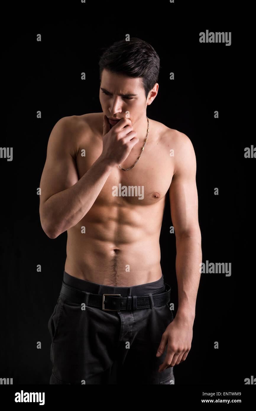 Demande beau jeune homme torse nu avec la main sous son menton, la pensée de doute. Sur fond noir Banque D'Images