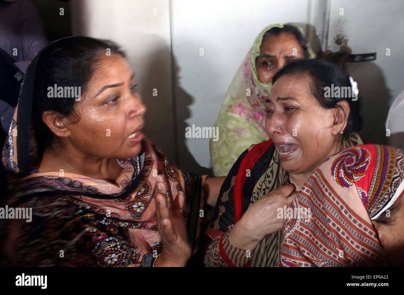Karachi, Pakistan. 12 mai, 2015. Des proches de l'ancien Muttahida Qaumi Movement (MQM) Activiste Saulat Mirza réagir pleurer sur le déplacement de son corps, qui a été pendu à la prison de Mach, mardi, dans une affaire de meurtre triple a été dit d'être calme et composé à l'échafaud, à l'Aéroport International Jinnah Muttahida Qaumi Movement dans Ancien (MQM) Activiste Saulat Mirza a été exécuté aujourd'hui matin à 4 h 30, de l'assassinat de l'ancien directeur général de la société KESC Shahid Hamid, son chauffeur et garde côtière canadienne en 1997. Banque D'Images