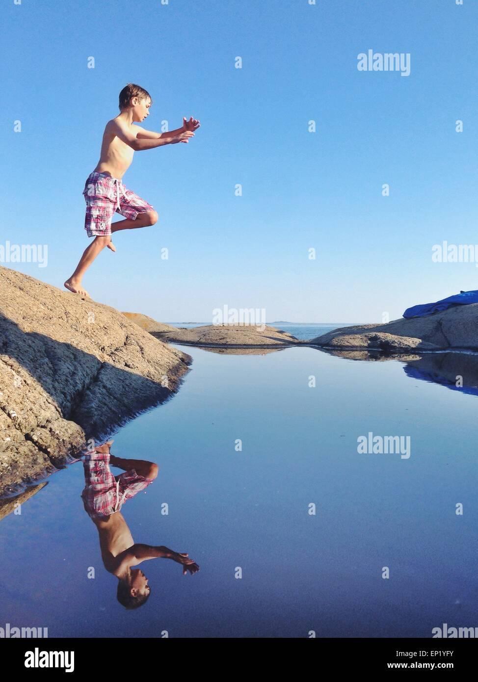Garçon sautant un rocher dans la mer Photo Stock