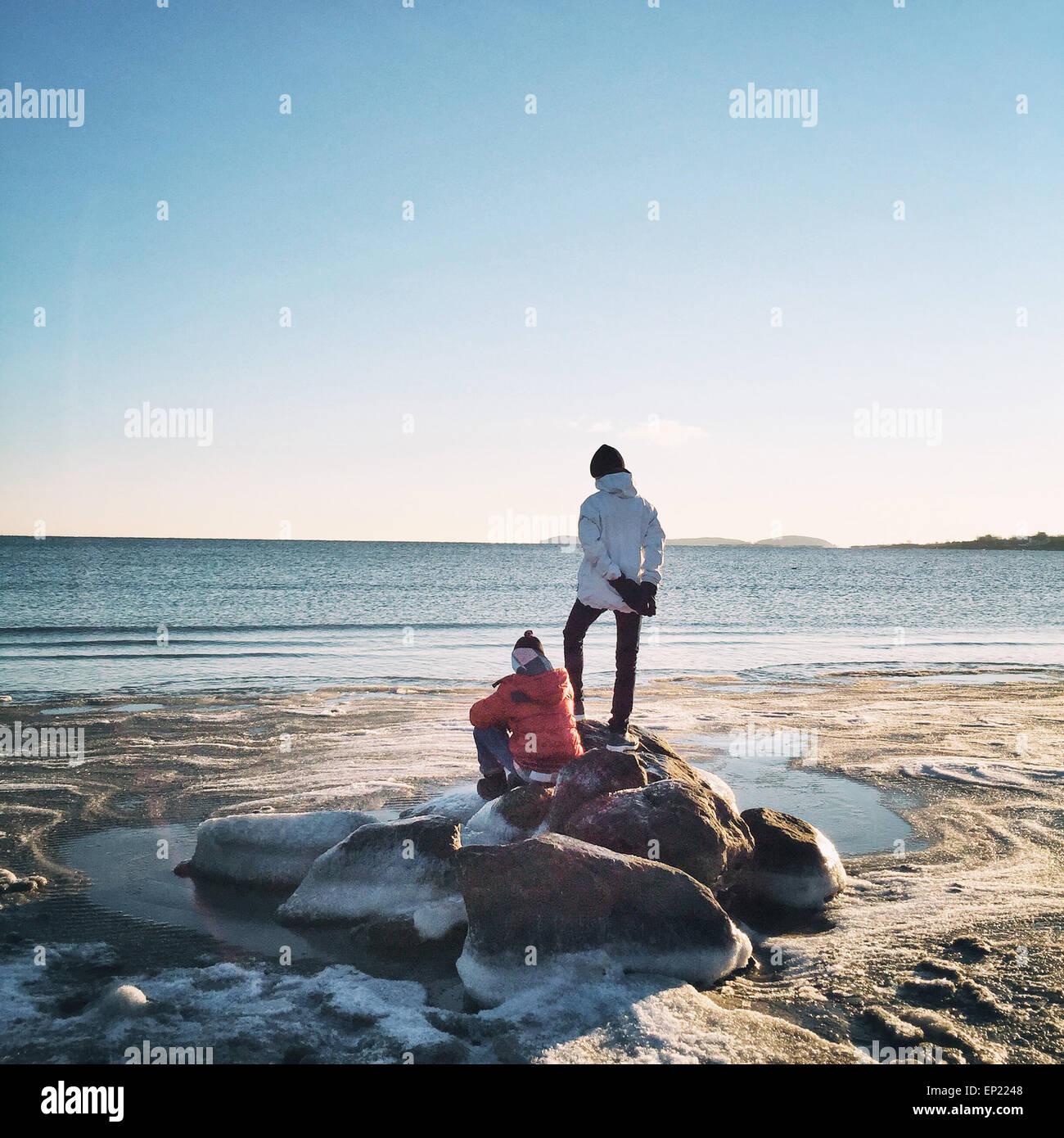 Vue arrière de deux garçons sur les roches par la mer Photo Stock