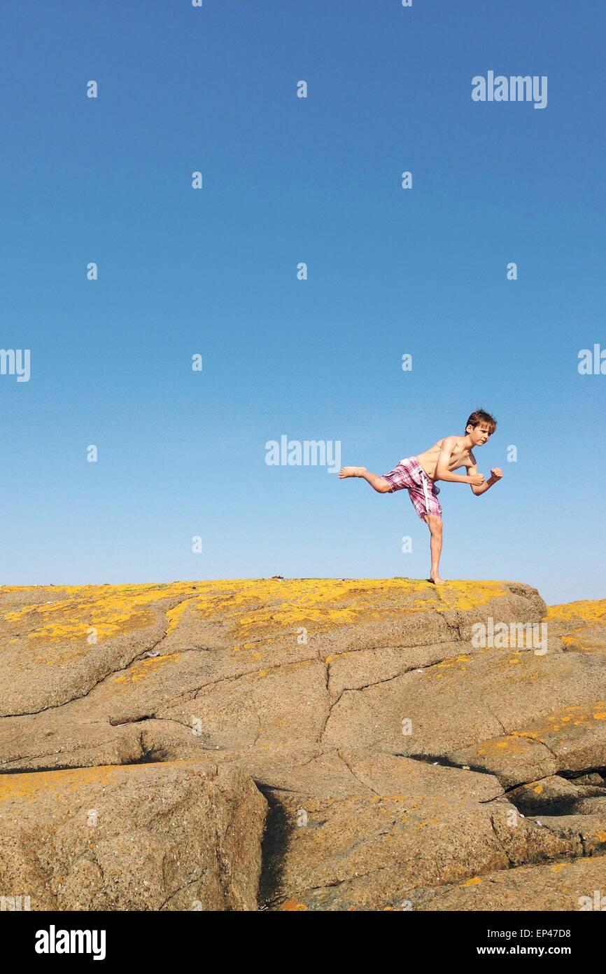 Garçon debout sur une jambe sur un rocher Photo Stock