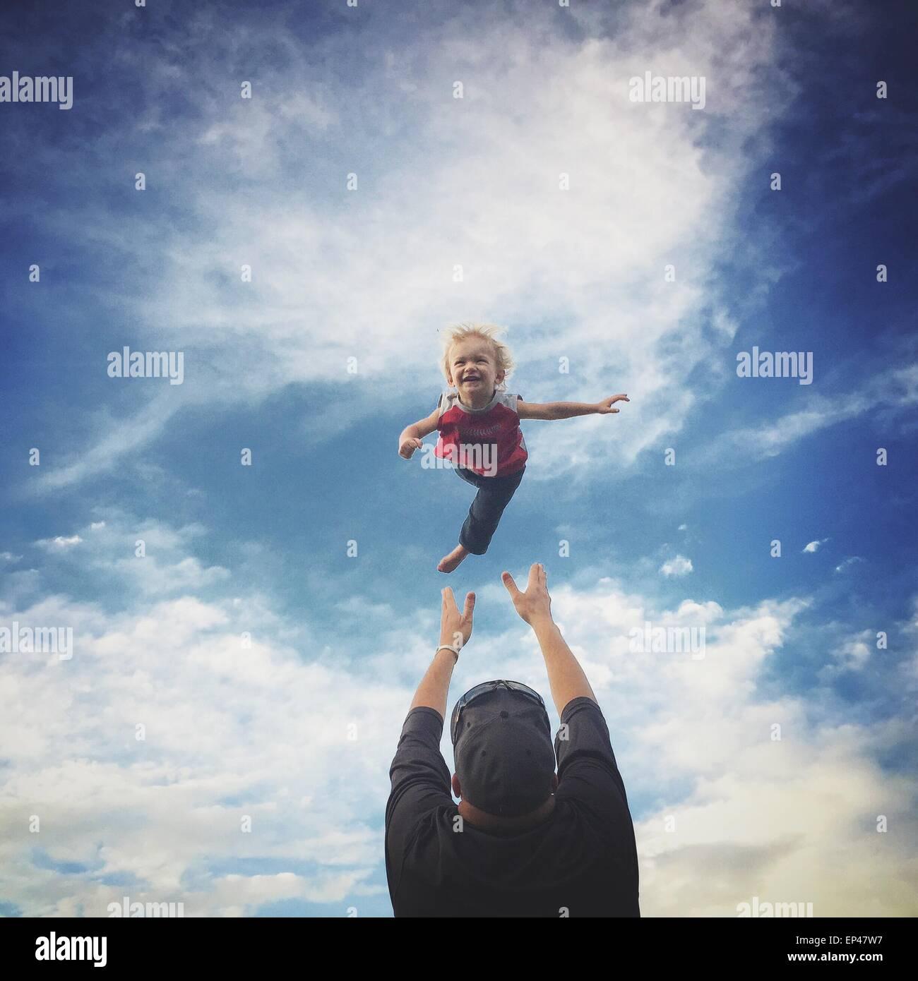 Père de jeter son fils dans l'air Photo Stock