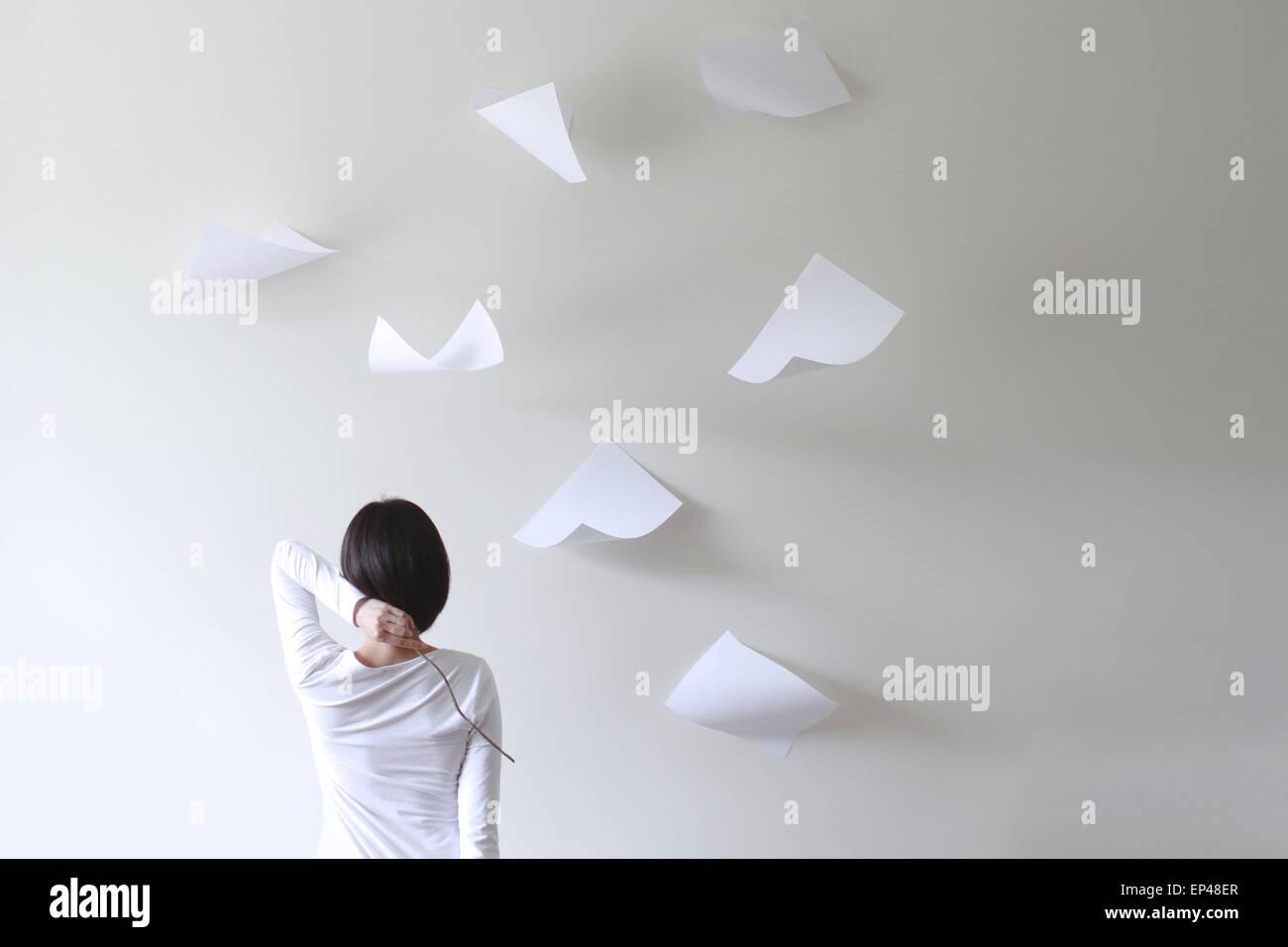 Vue arrière d'une femme tenant un bâton derrière la tête avec des morceaux de papier volant Photo Stock