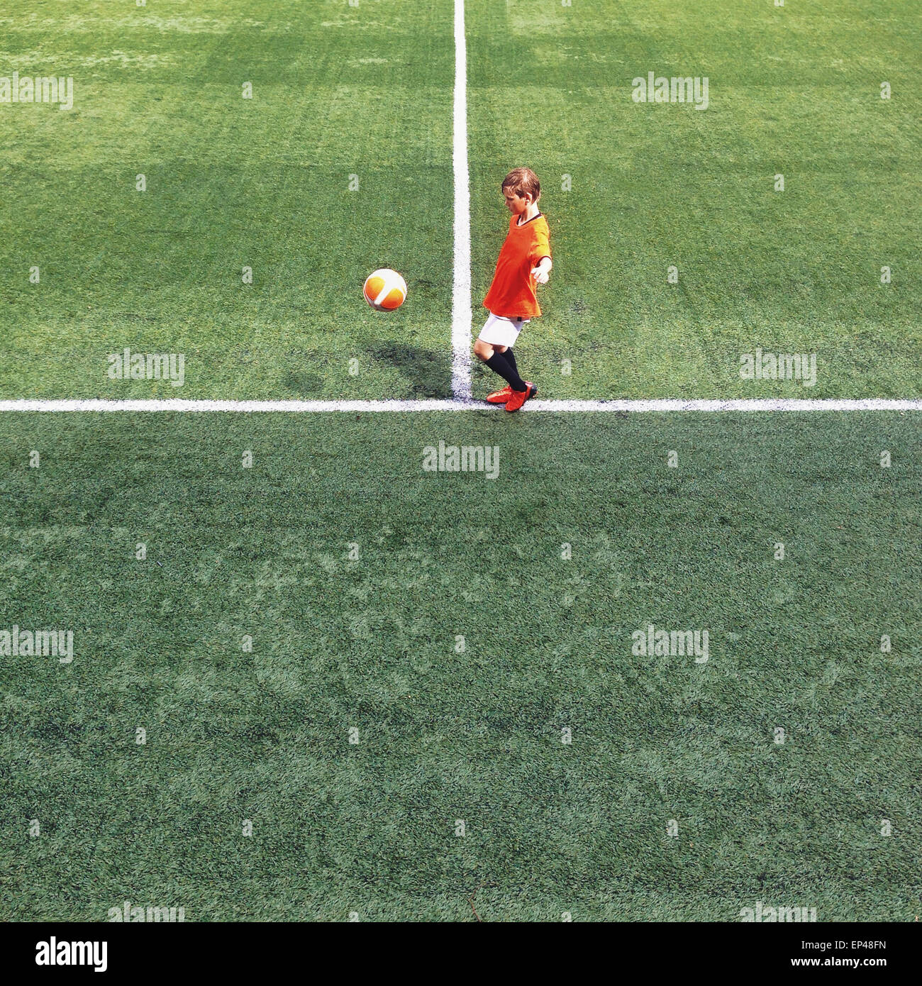 Vue latérale d'un enfant sur un terrain de football Photo Stock