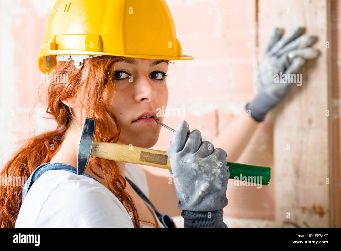 Femme avec casque de chantier tenant un marteau dans sa main Photo Stock